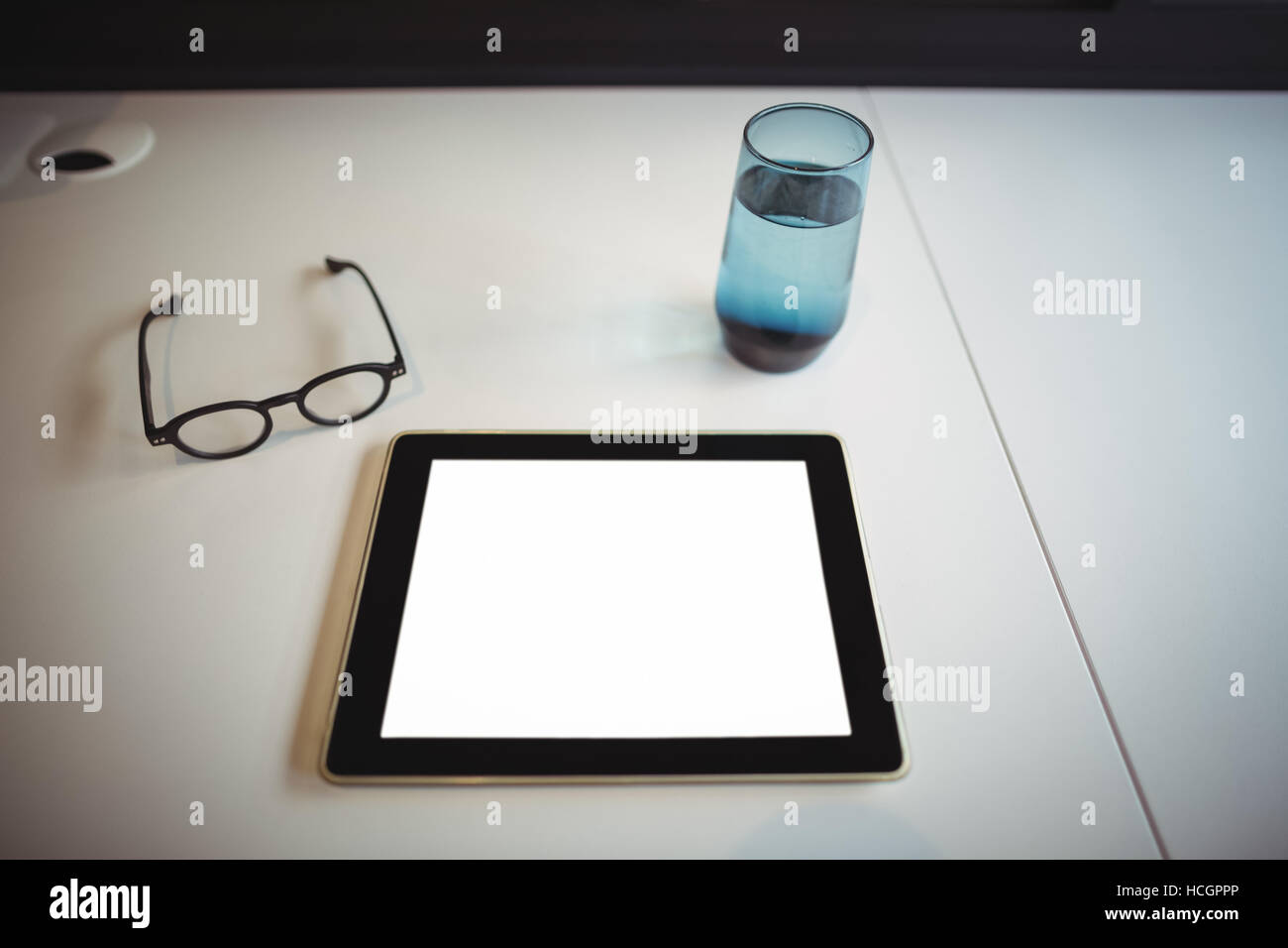 Digital tablet with spectacle and glass of water on office desk - Stock Image