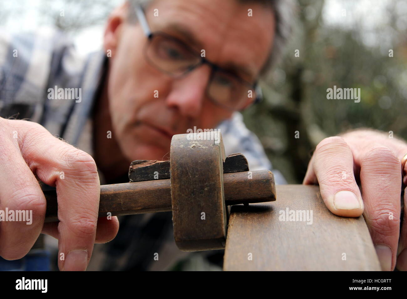 Traditional woodworker using antique brass and wood mortise gauge - Stock Image