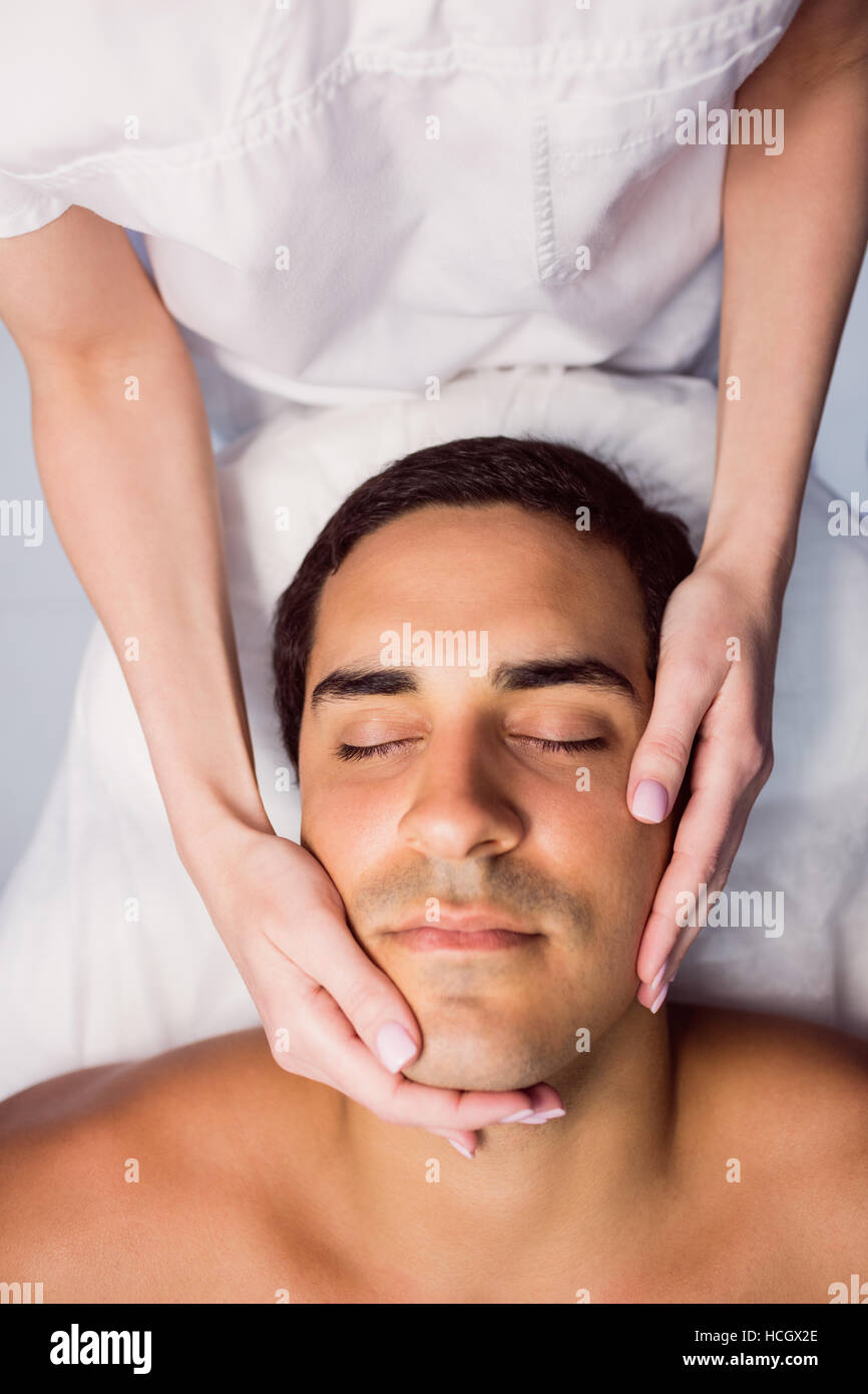 Man getting a facial massage at clinic - Stock Image