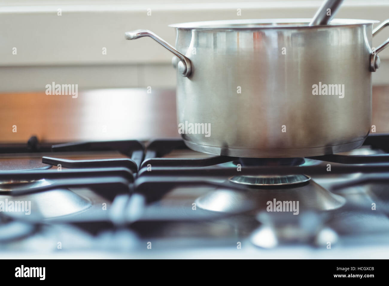 Cooking pot kept on a stove while cooking - Stock Image