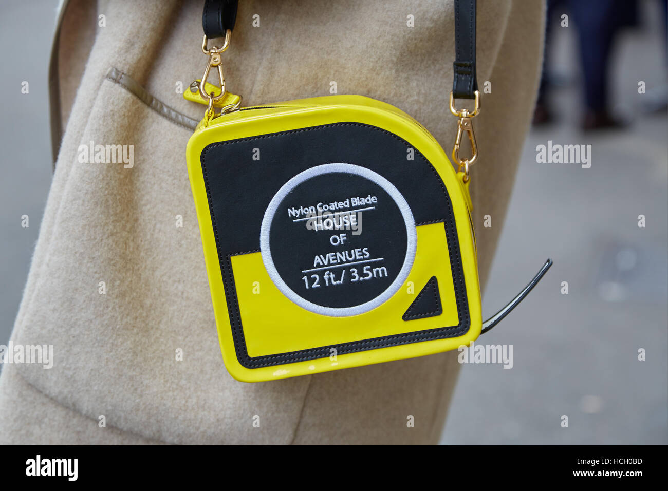 Woman with yellow bag with measuring tape shape before Max Mara fashion show, Milan Fashion Week street style on - Stock Image