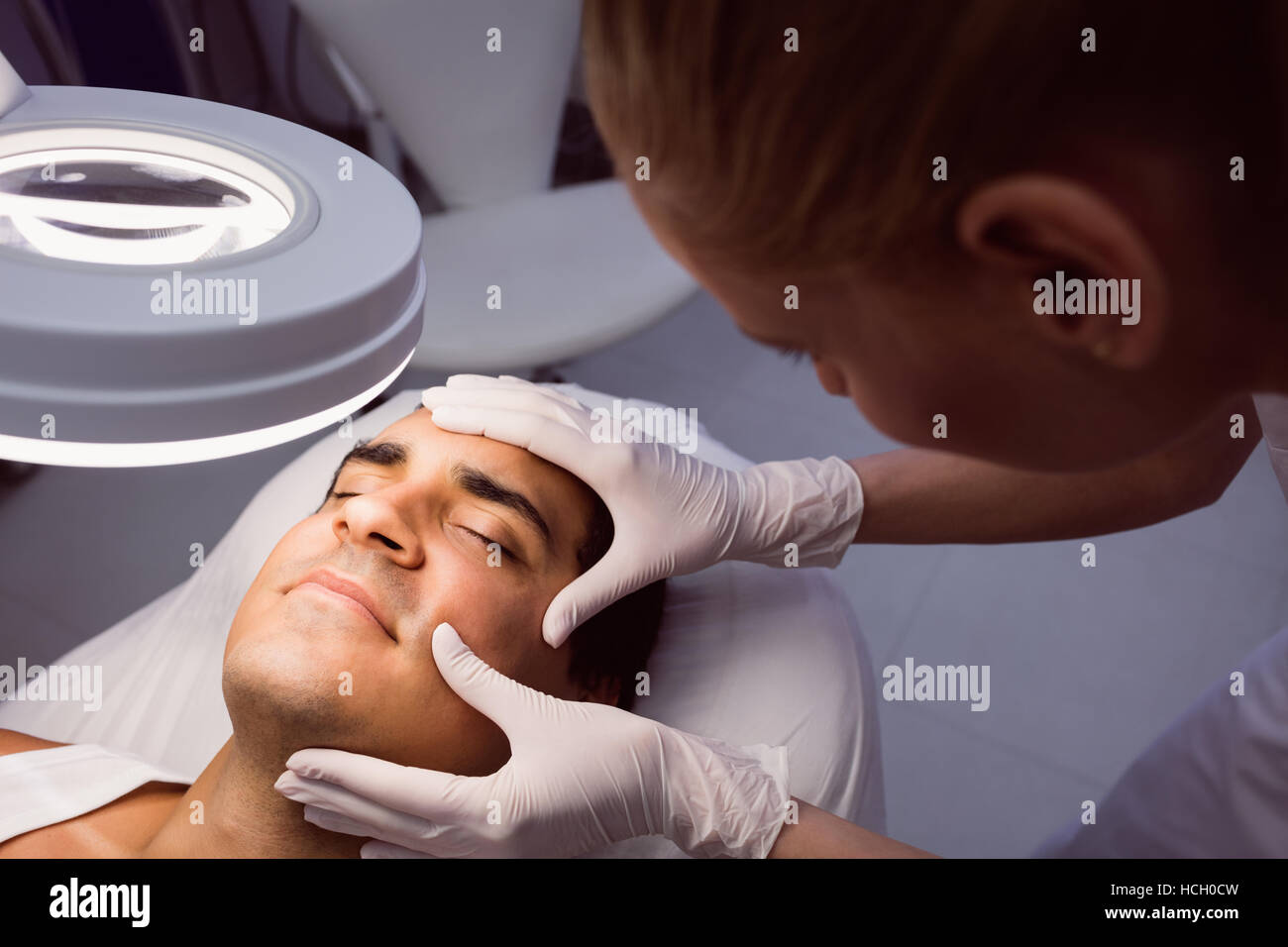 Doctor examining mans face for cosmetic treatment - Stock Image