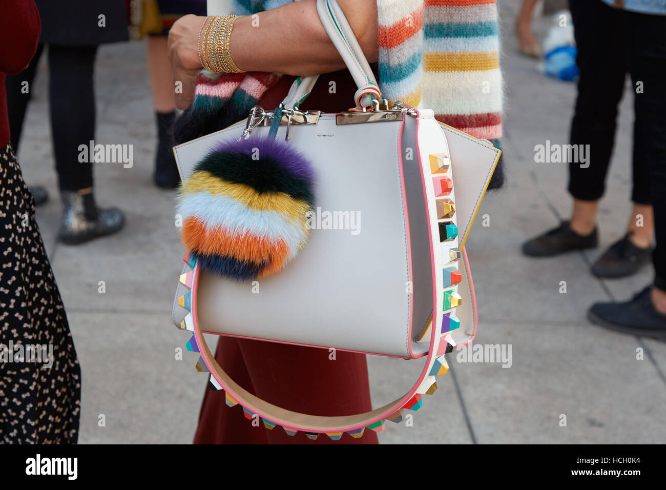 Woman with white leather bag with colorful fur accessory before Cristiano Burani fashion show, Milan Fashion Week - Stock Image
