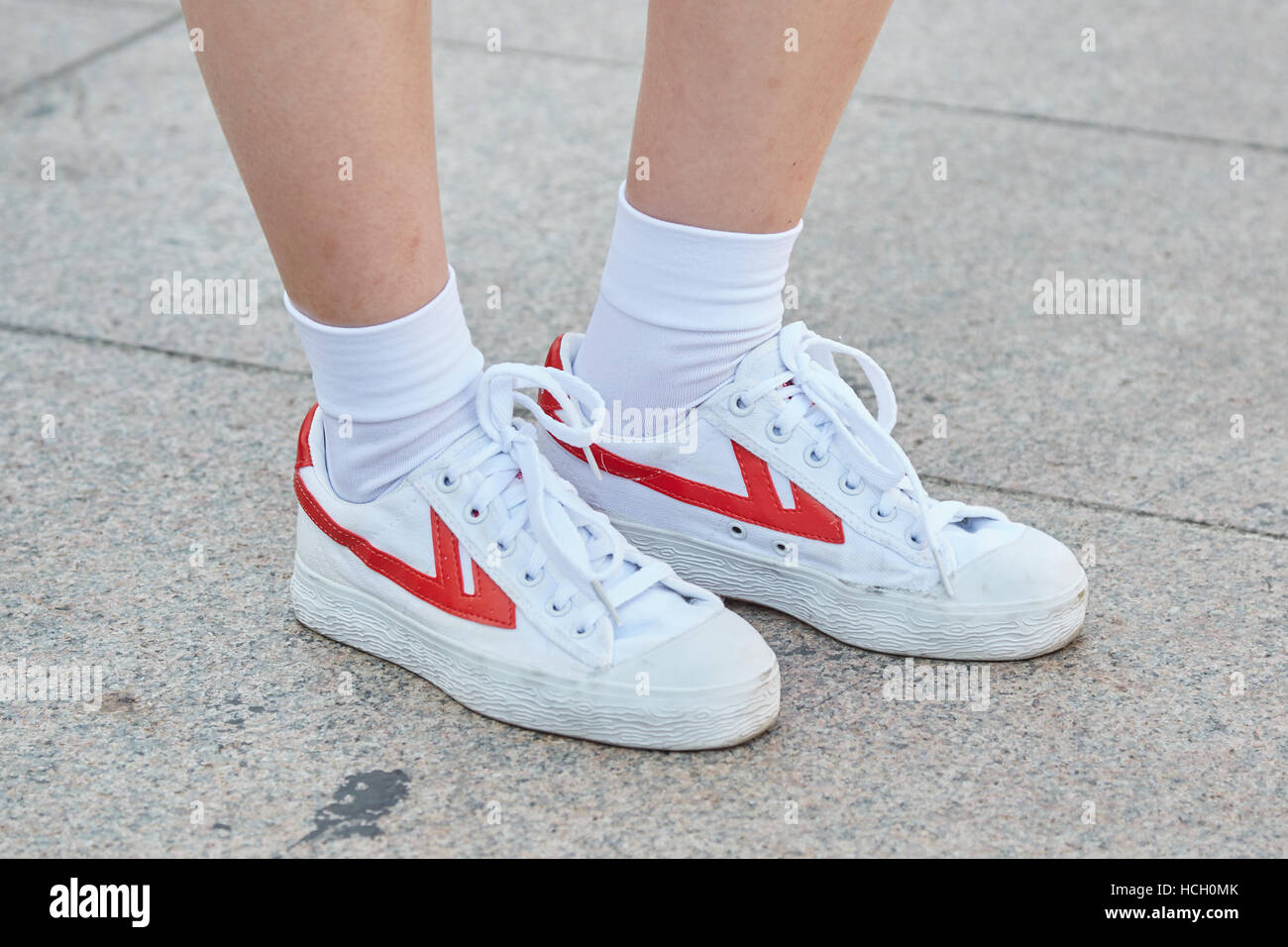 Woman with white and red sneakers before Cristiano Burani fashion show, Milan Fashion Week street style on September - Stock Image