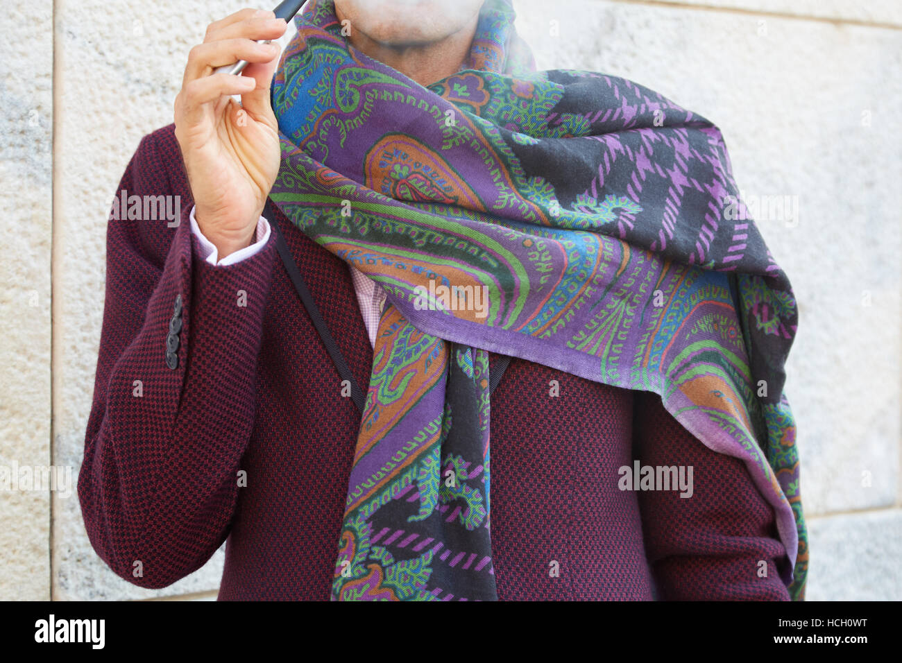 Elegant man smoking with floral pattern scarf before Cristiano Burani fashion show, Milan Fashion Week street style - Stock Image
