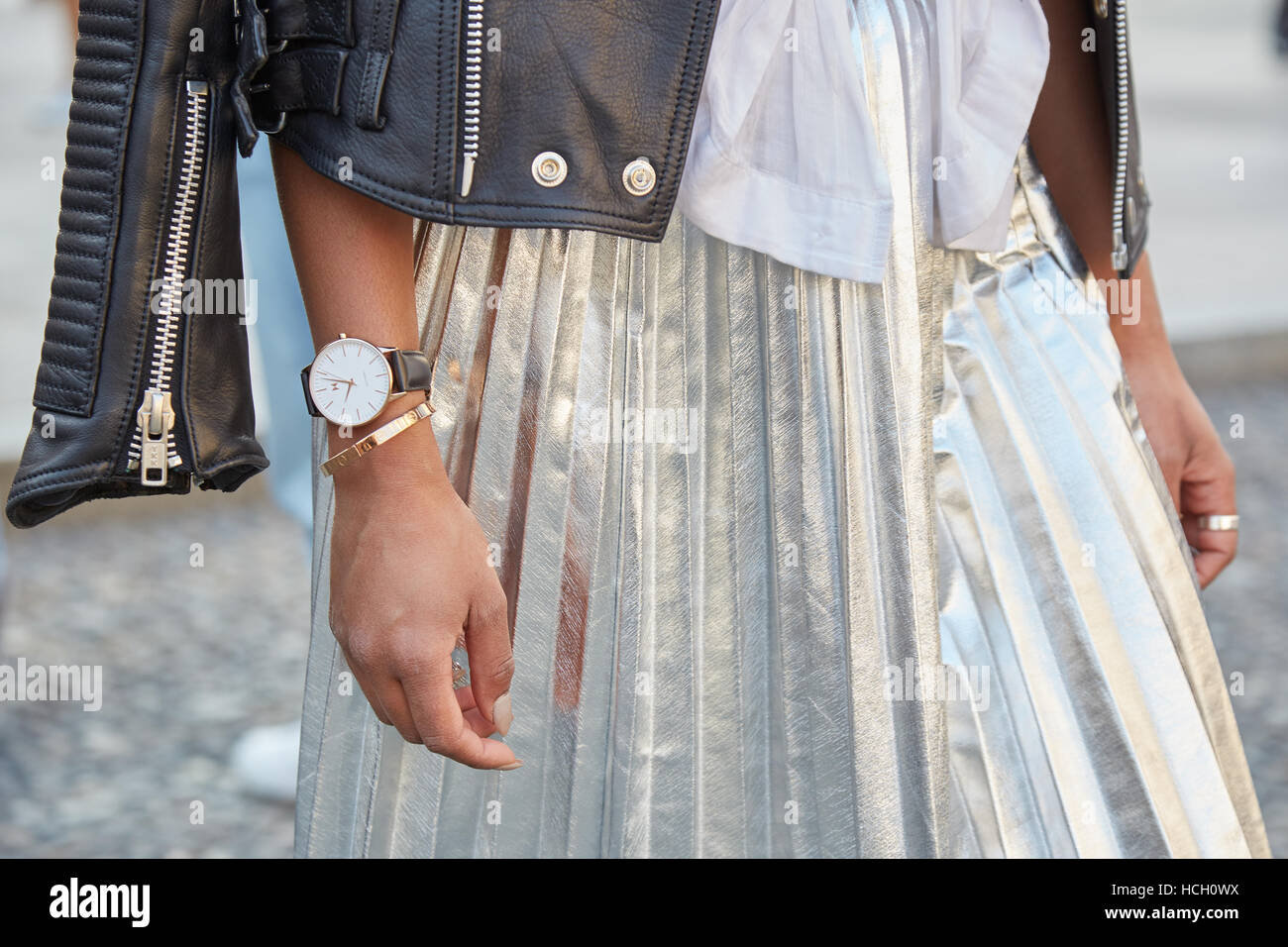 Woman with shiny silver skirt and black leather jacket before Cristiano Burani fashion show, Milan Fashion Week - Stock Image