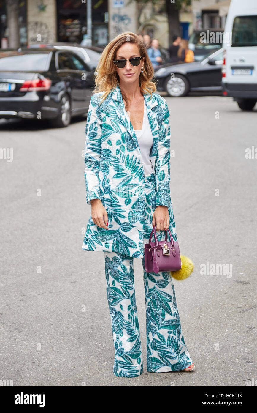 Woman with blue floral design jacket and trousers before Giorgio Armani fashion show, Milan Fashion Week street - Stock Image