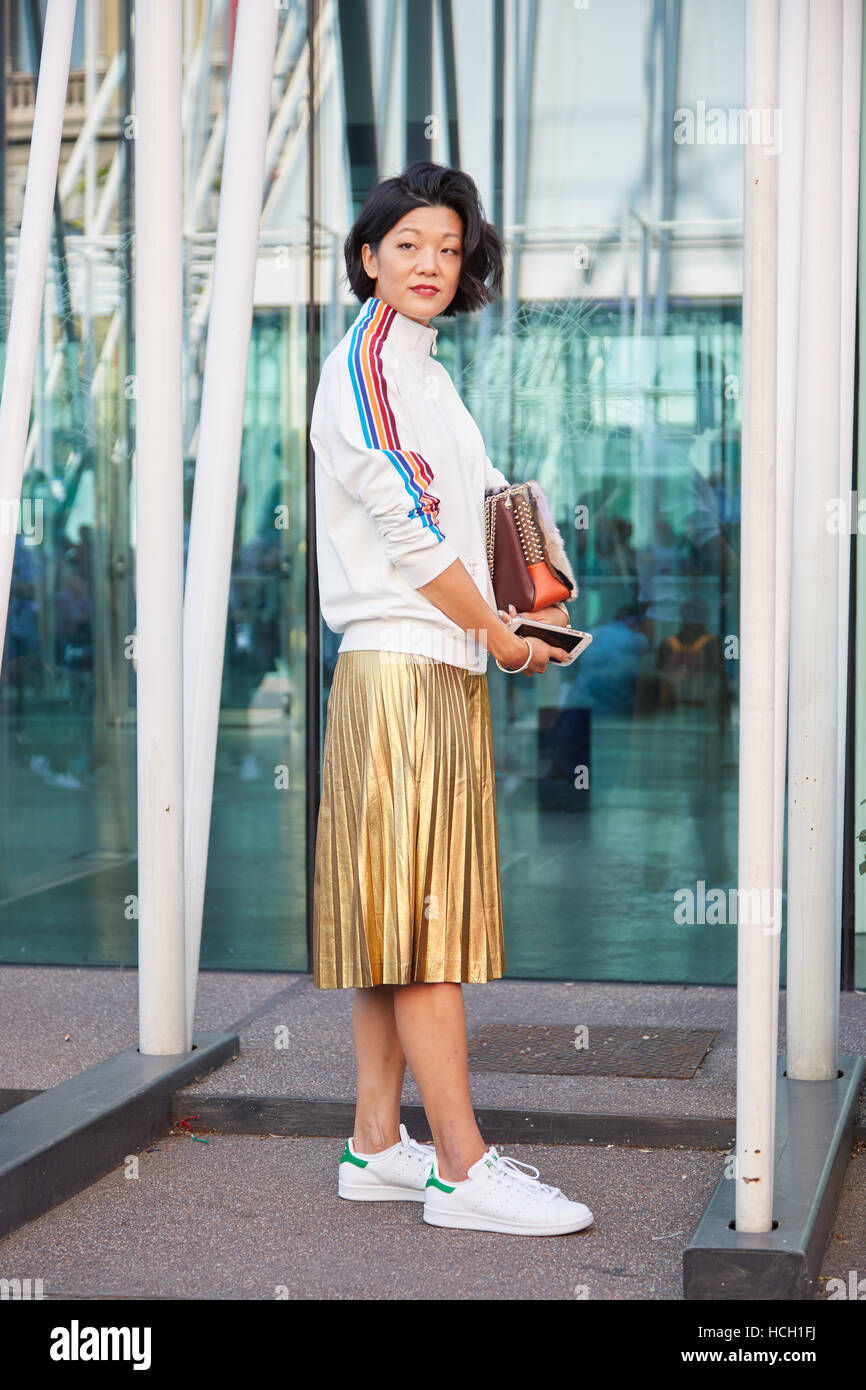 Woman with golden skirt and white Adidas sneakers before Jil Sander fashion show, Milan Fashion Week street style - Stock Image