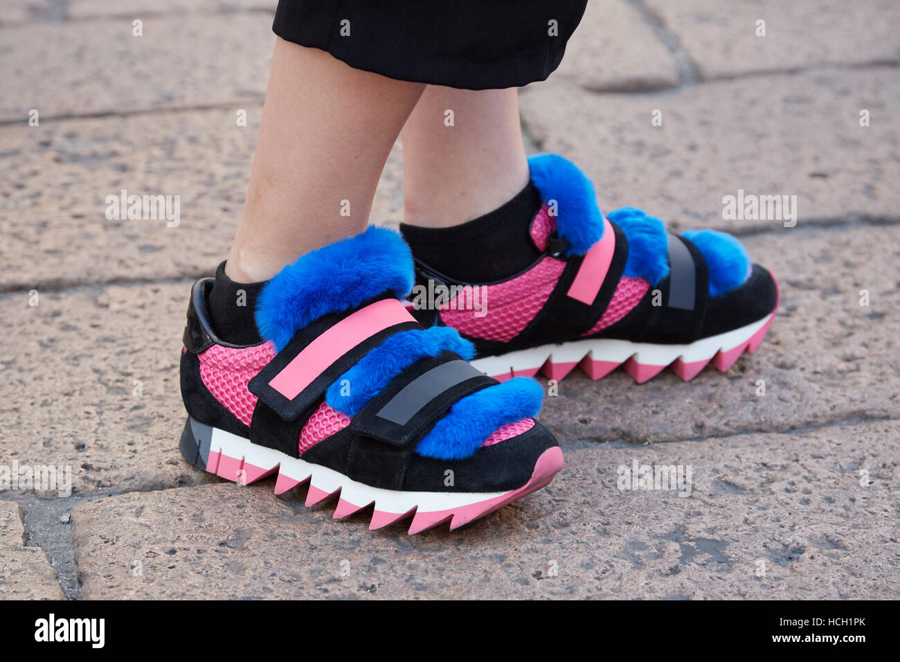 Woman with black, pink Dolce Gabbana shoes with blue fur before Salvatore Ferragamo fashion show, Milan Fashion - Stock Image