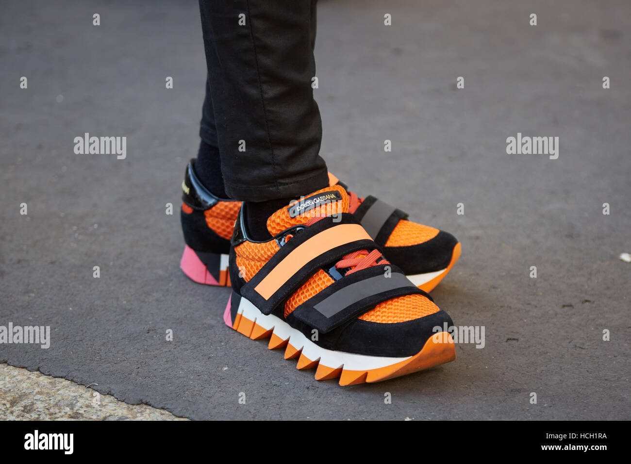 Woman with Dolce Gabbana orange and black shoes before Salvatore Ferragamo fashion show, Milan Fashion Week street - Stock Image