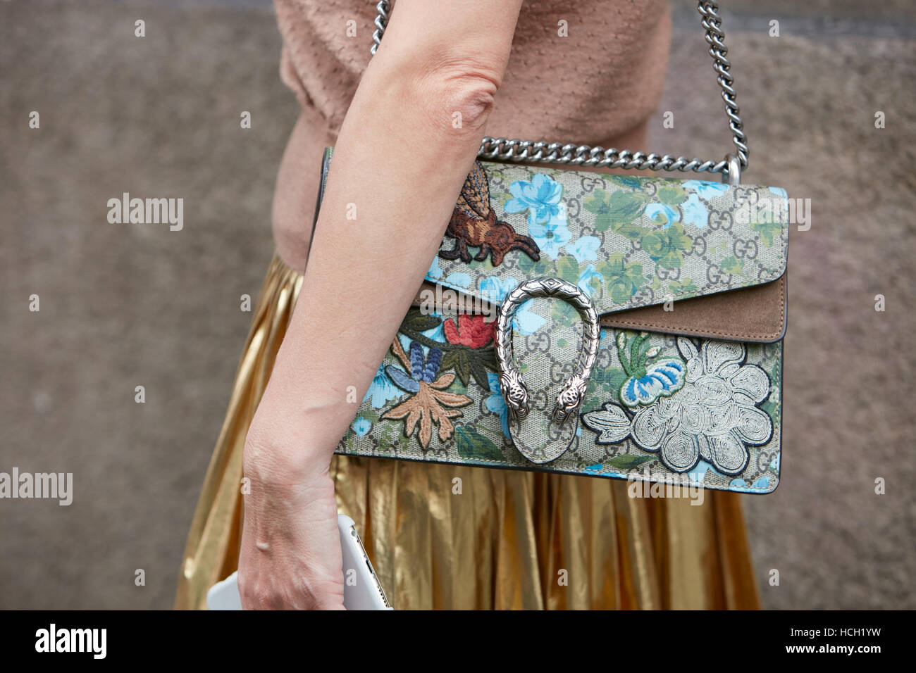 Woman with Gucci bag with floral decoration and golden skirt before Max Mara fashion show, Milan Fashion Week street - Stock Image
