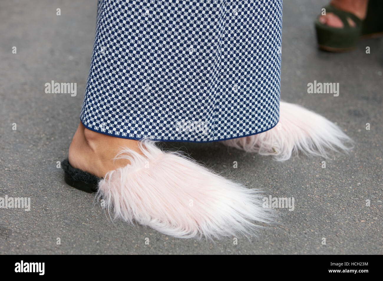 Woman with pink fur shoes and black and white pattern trousers before Max Mara fashion show, Milan Fashion Week - Stock Image