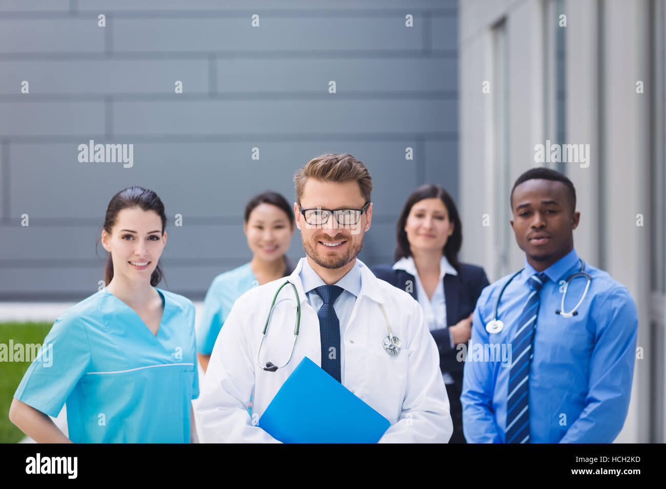 Team of doctors standing together in hospital premises - Stock Image