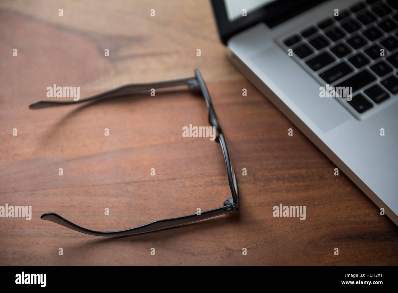Laptop and spectacle on table - Stock Image