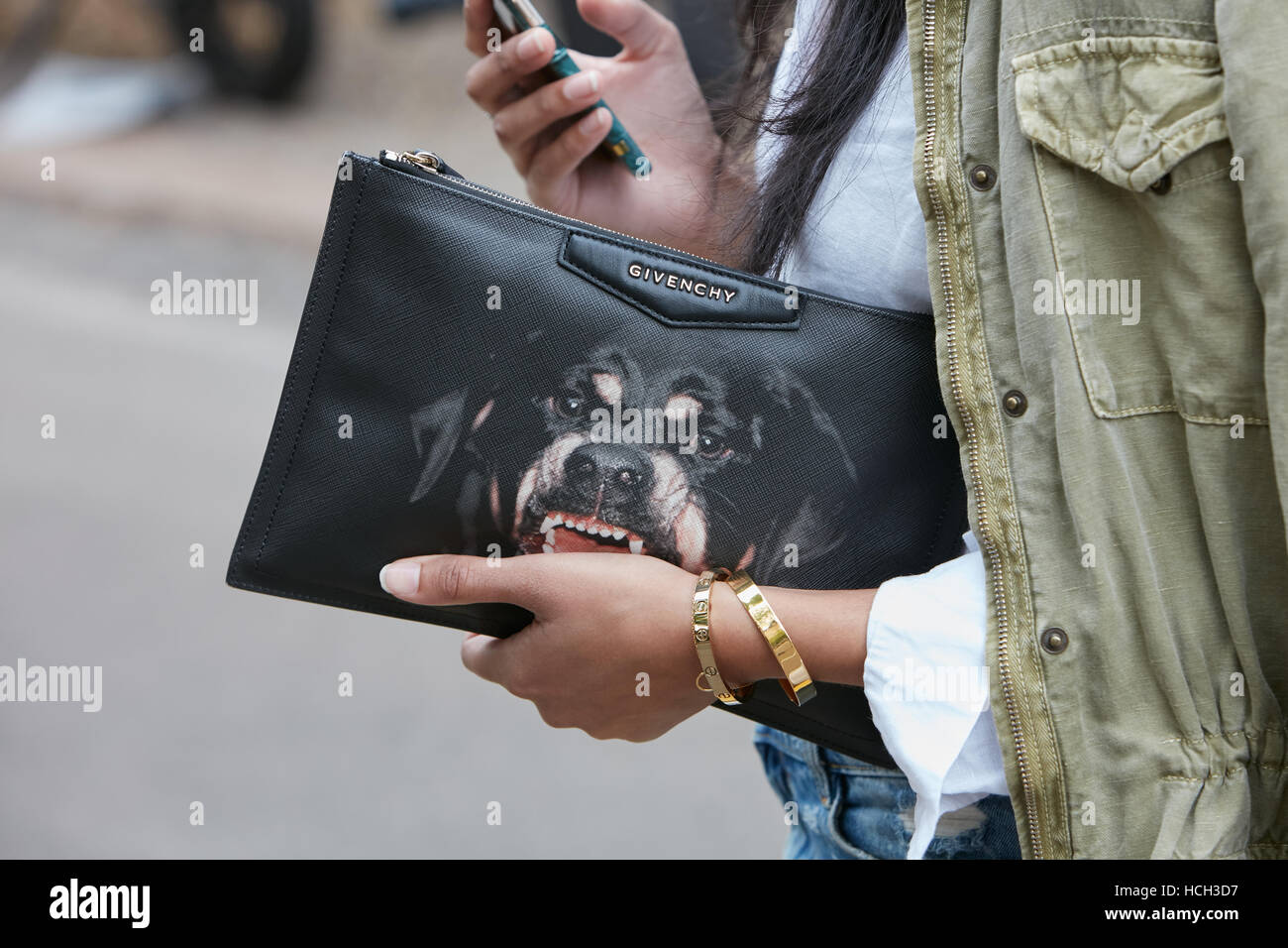 Woman with Givenchy bag with growling dog before Fendi fashion show, Milan Fashion Week street style on September - Stock Image