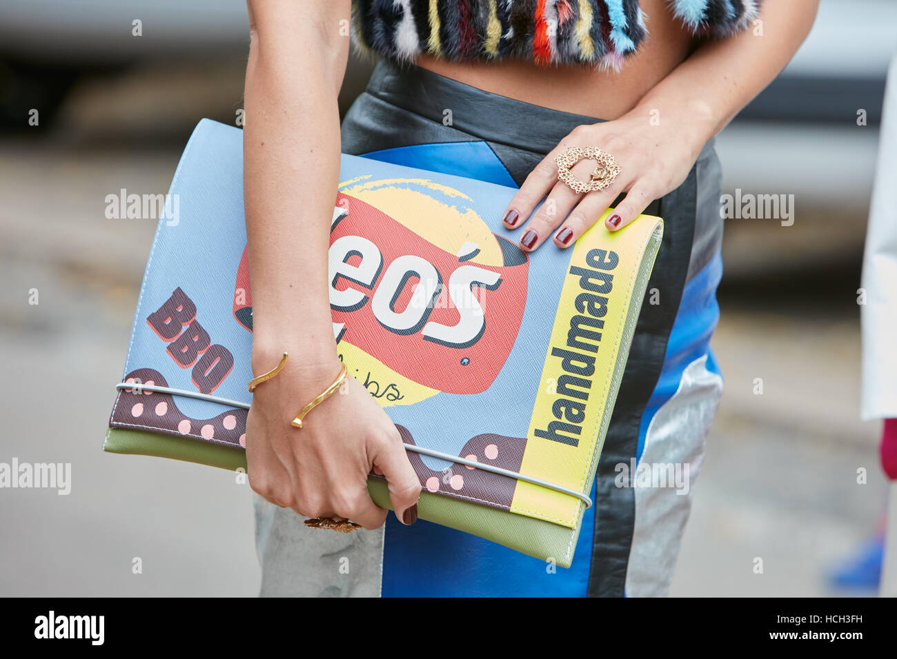Woman with colorful bag with handmade writing before Fendi fashion show, Milan Fashion Week street style on September - Stock Image