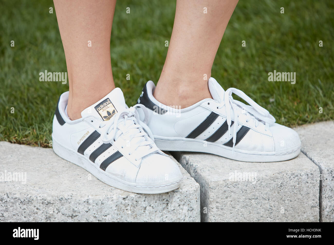 Woman with white Adidas superstar sneakers before Giorgio Armani fashion show, Milan Fashion Week street style on - Stock Image
