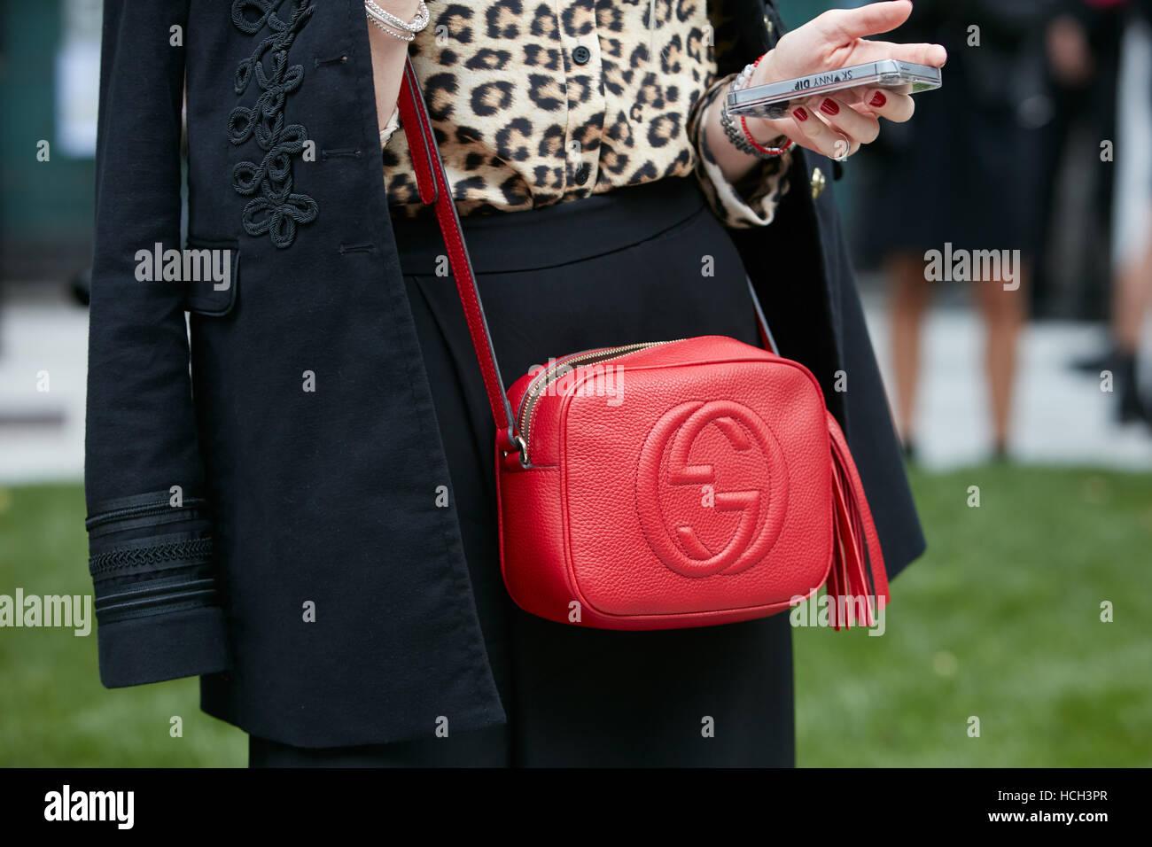 180a37aeff1 Woman with red Gucci leather bag before Giorgio Armani fashion show