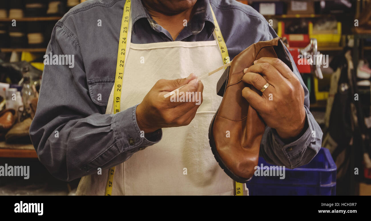 Mid section of shoemaker applying glue on shoe - Stock Image