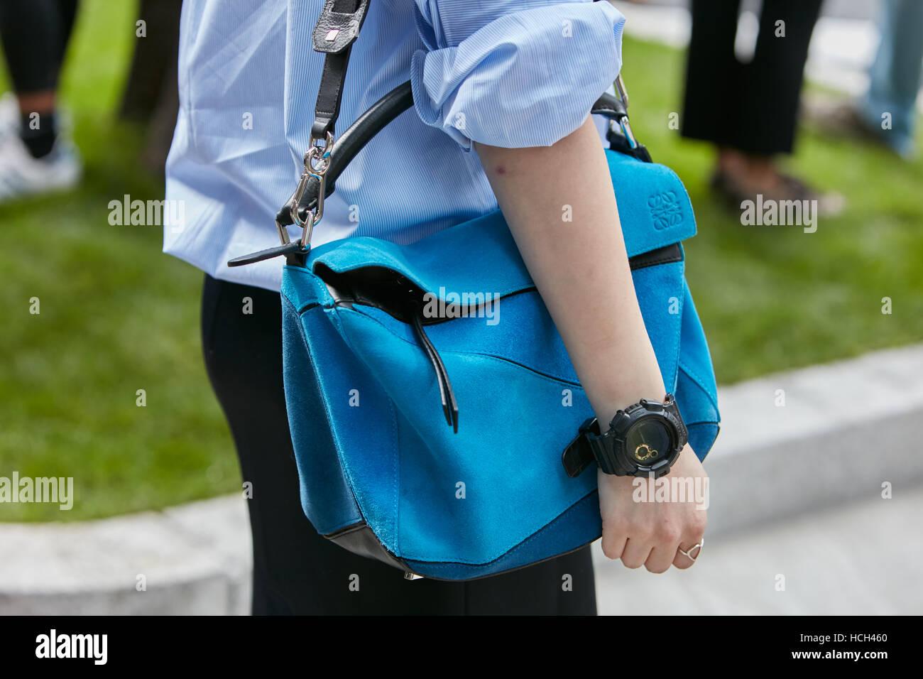 Woman with blue Loewe bag and Casio watch before Giorgio Armani fashion show, Milan Fashion Week street style on - Stock Image