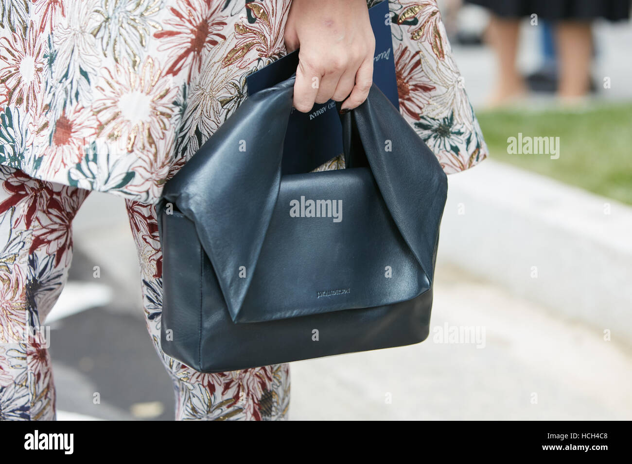 Woman with Anderson black leather bag before Giorgio Armani fashion show, Milan Fashion Week street style on September - Stock Image