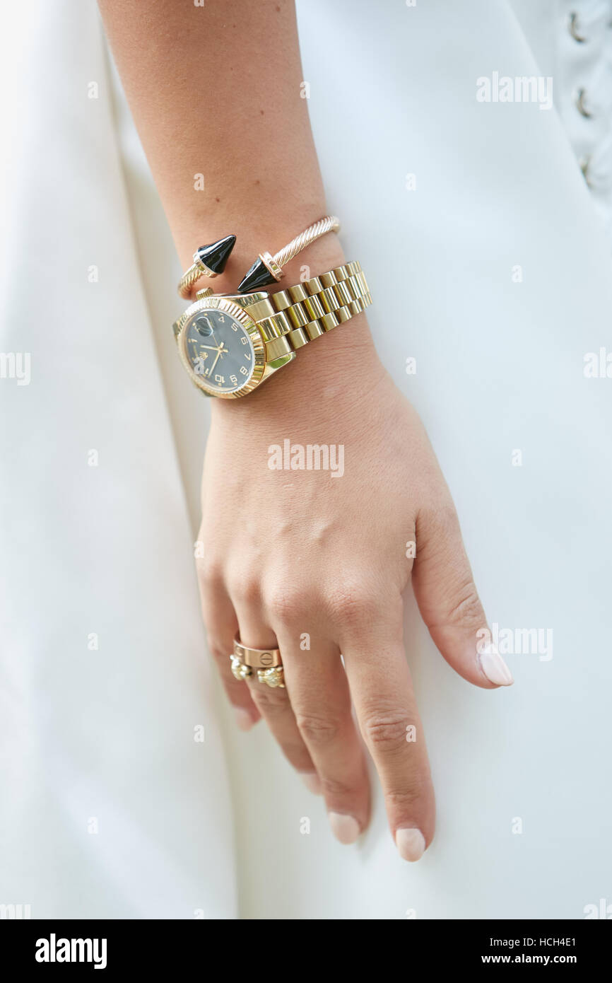 Woman with golden Rolex watch and jewels before Giorgio Armani fashion show, Milan Fashion Week street style on - Stock Image