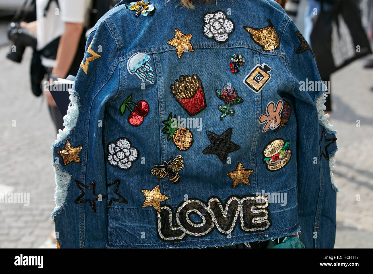 Woman with blue jeans jacket with Love writing before Giamba fashion show, Milan Fashion Week street style on September - Stock Image