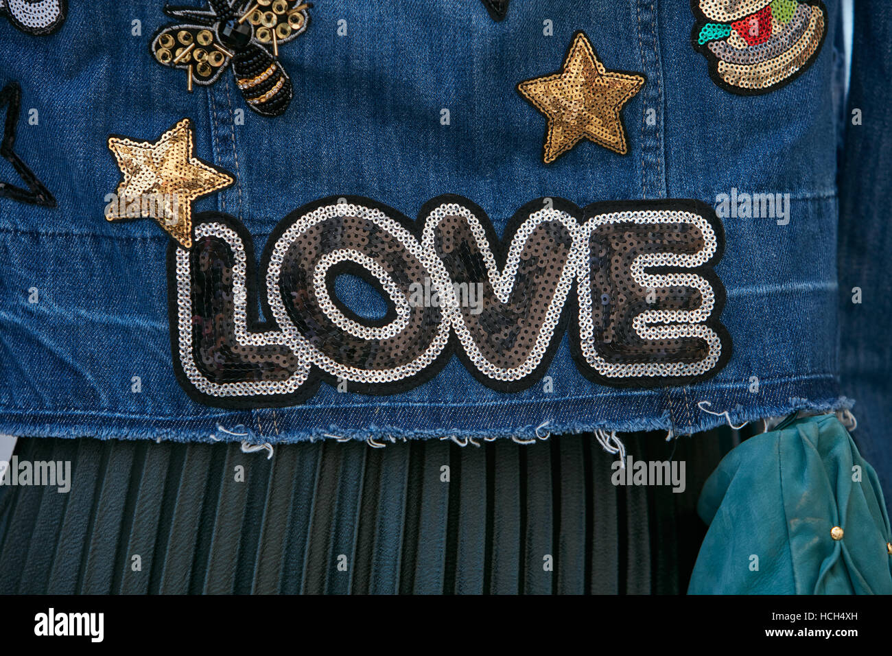 Woman with blue jeans jacket with Love sequin writing before Giamba fashion show, Milan Fashion Week street style - Stock Image