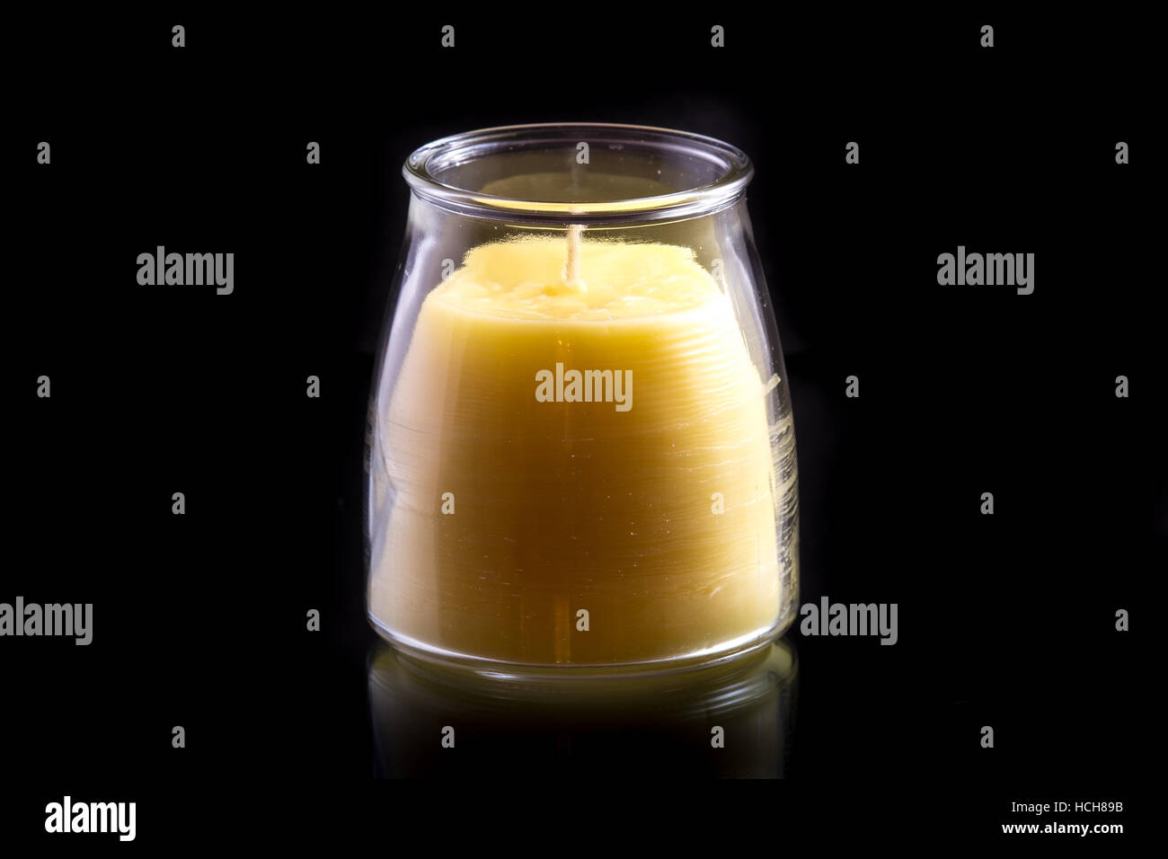 Beeswax candle (unlit) in a glass jar on a black background with a subtle reflection - Stock Image