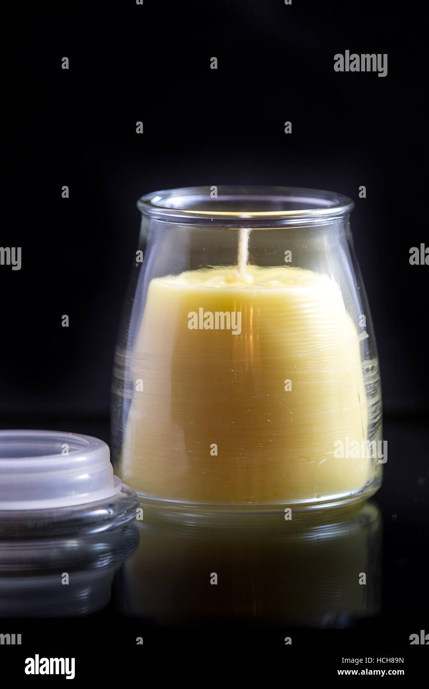 Beeswax candle (unlit) in a glass jar on a black background with a subtle reflection and a lid. - Stock Image