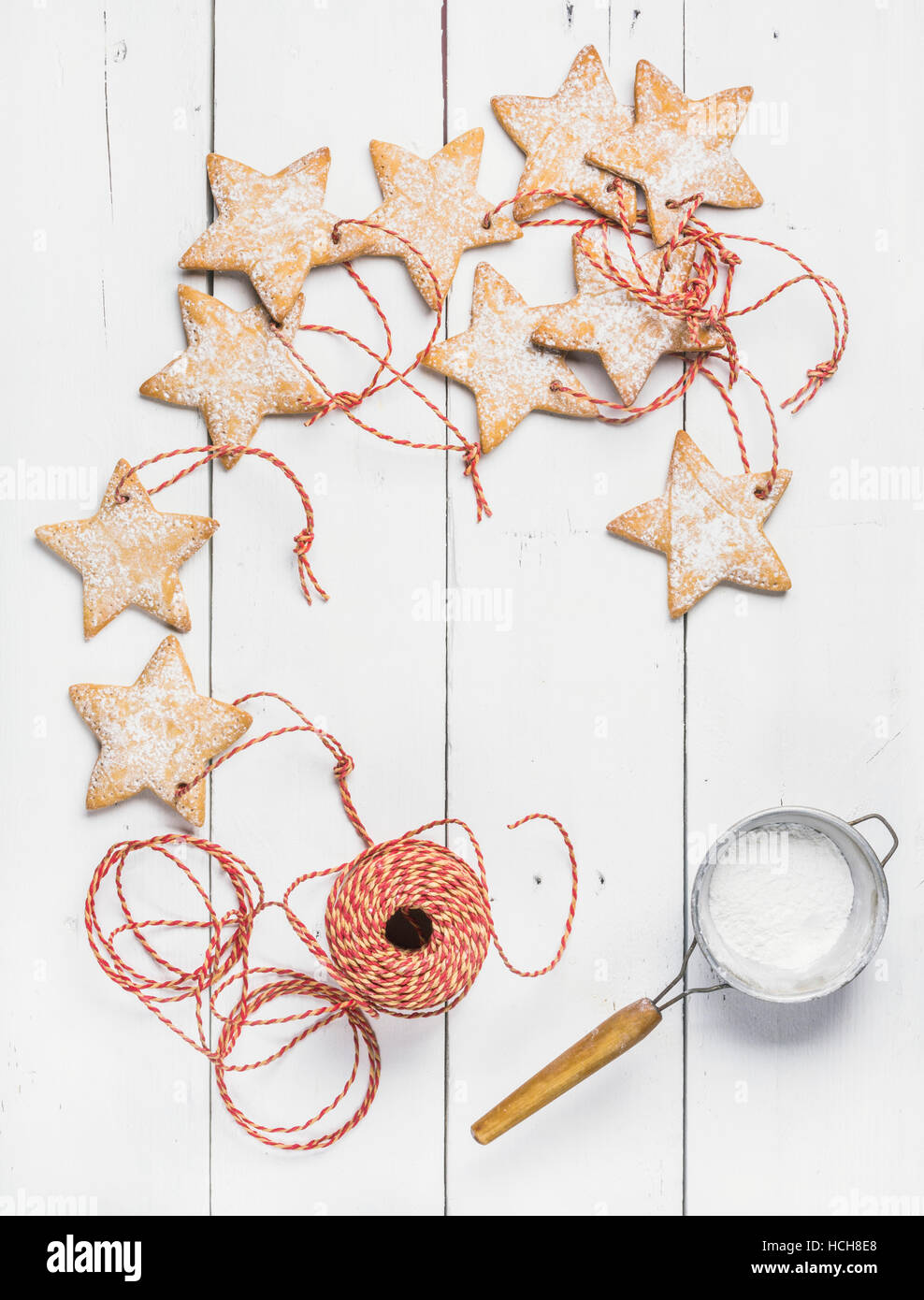 Christmas homemade gingerbread star shaped cookies with sugar powder in sieve and red decoration rope over white - Stock Image