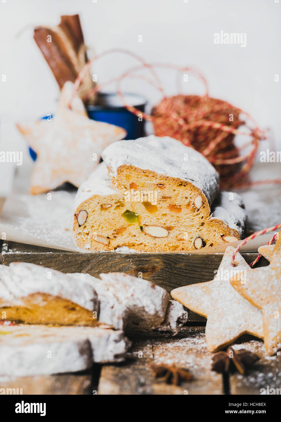 Piece of Traditional German Christmas cake Stollen with festive gingerbread star shaped cookies, selective focus, - Stock Image