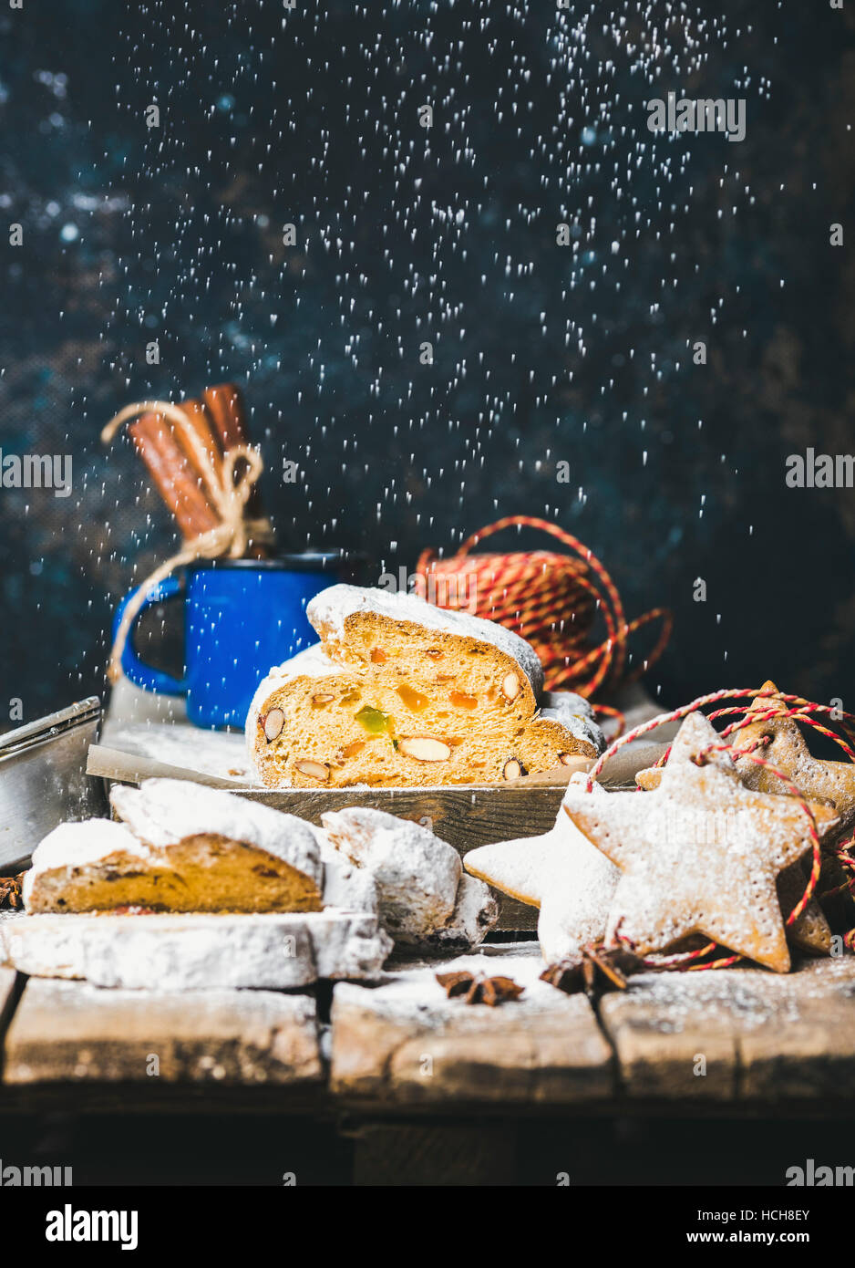 Piece of Traditional German Christmas cake Stollen with festive gingerbread star shaped cookies and falling sugar - Stock Image