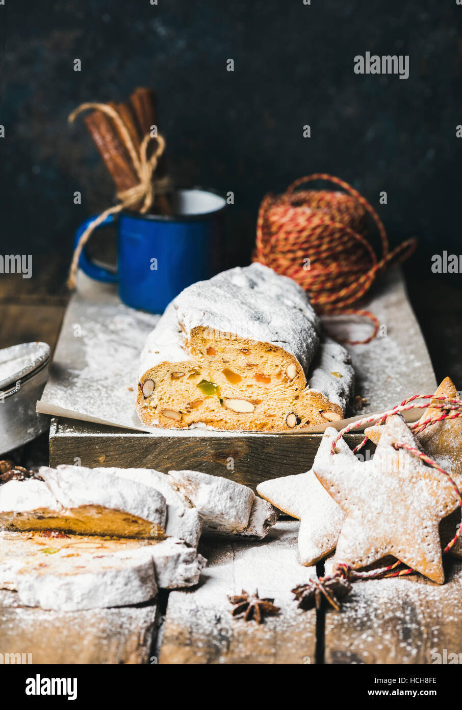 Traditional German Christmas cake Stollen with festive gingerbread cookies, selective focus, dark blue grunge background, - Stock Image