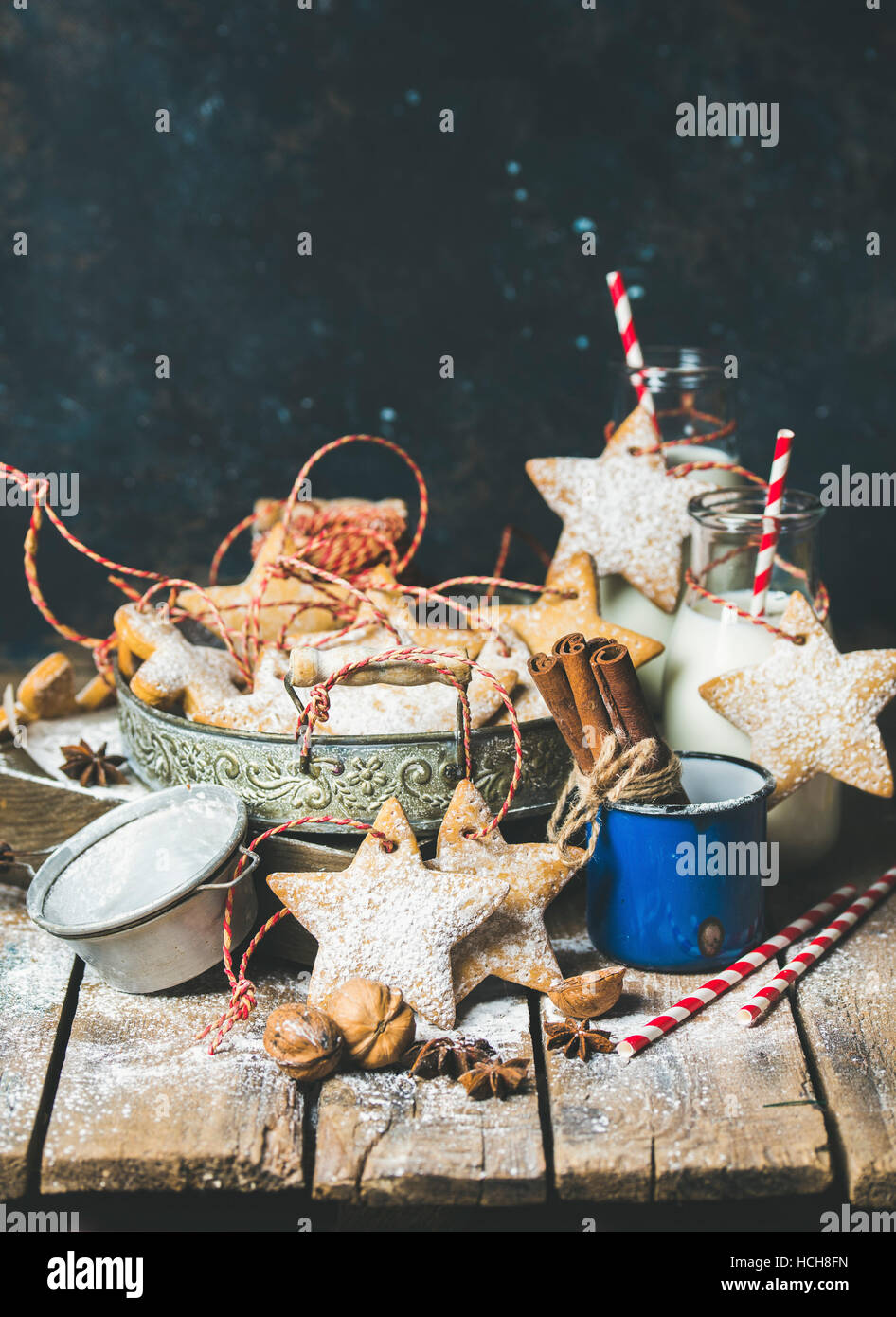 Christmas festive gingerbread cookies or biscuits in vintage tray, decoration rope, nuts, spices, milk for Santa in bottles, sugar powder. Selective f Stock Photo