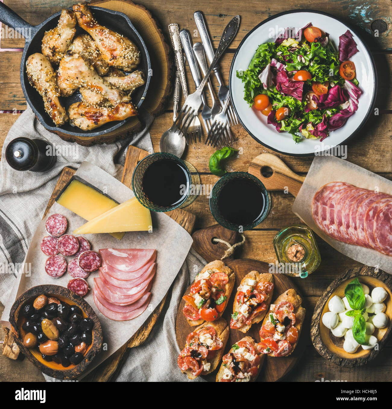 Home dinner, party table arrangement. Rustic table set with salad, olives, chicken, tomato, feta cheese brushettas, - Stock Image
