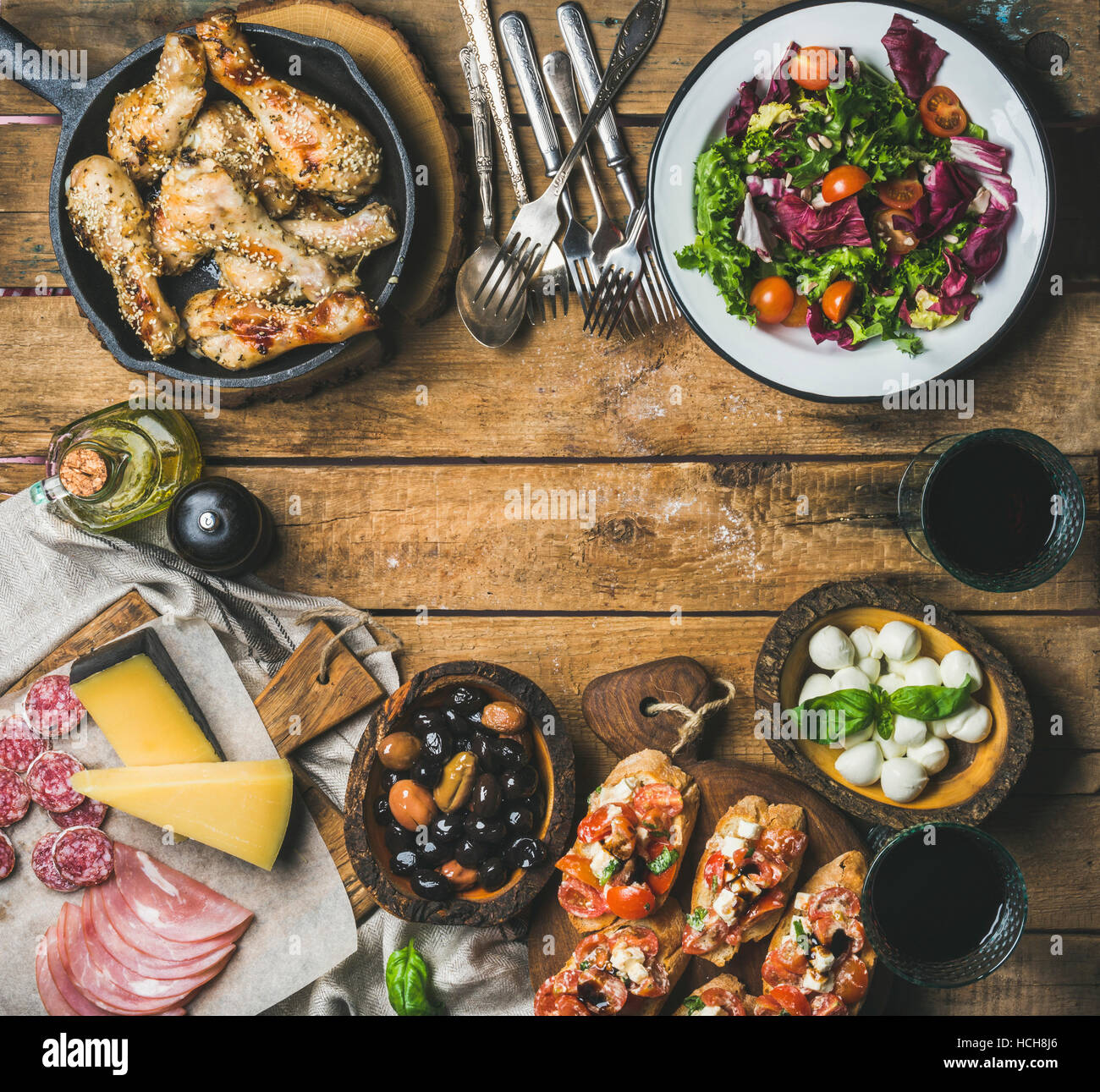 Party table arrangement. Rustic table set with vegetable salad, olives, chicken, tomato and feta cheese brushettas - Stock Image