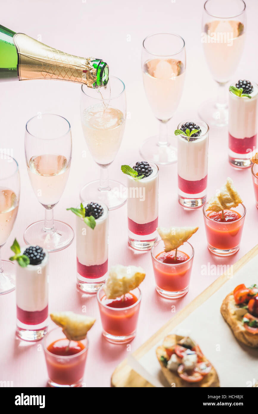 Various snacks, brushettas, gazpacho shots, desserts with berries and champagne pouring to glasses on corporate - Stock Image