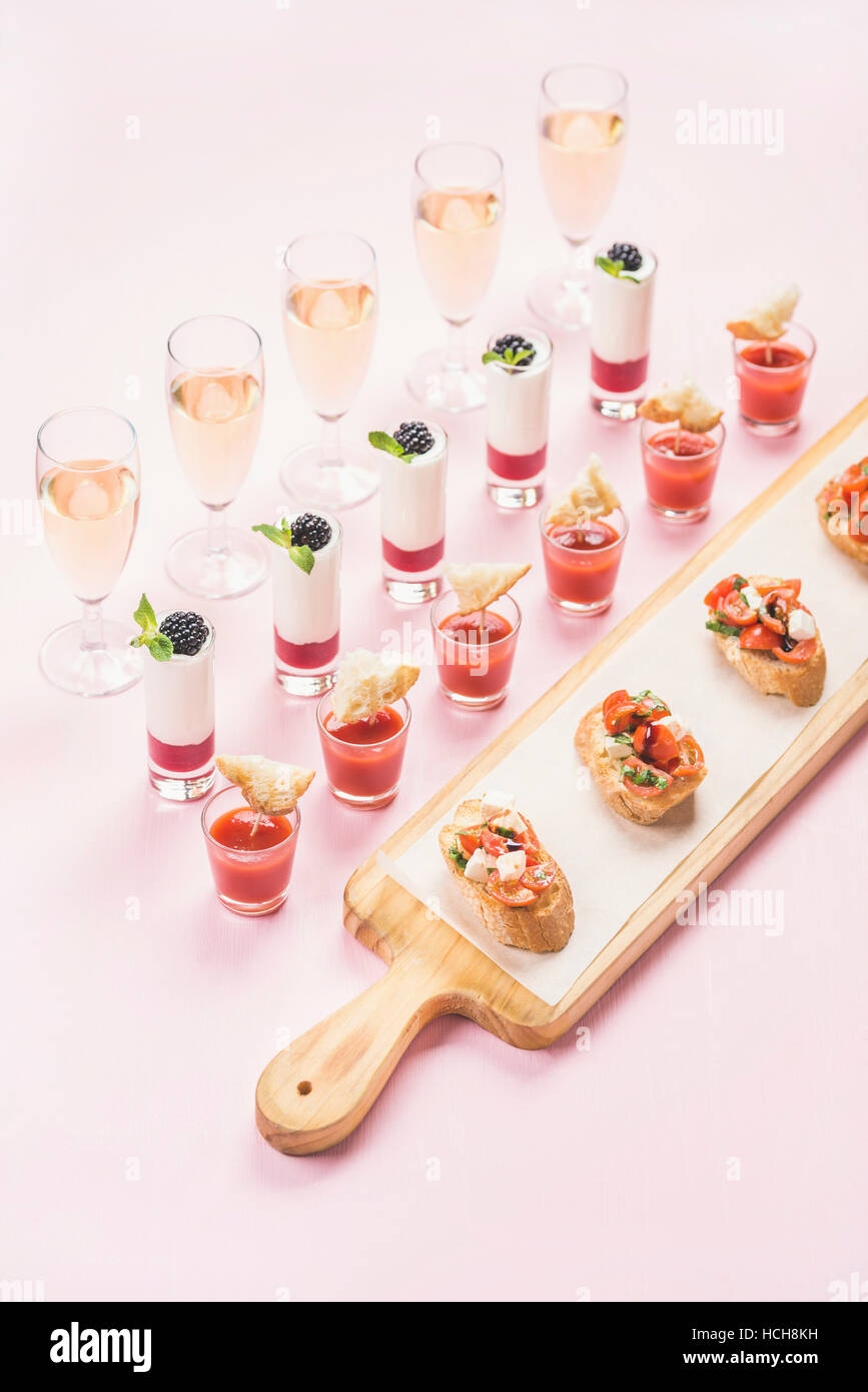 Catering, banquet or party food concept. Various snacks, brushetta sandwiches, gazpacho shots, desserts with berries - Stock Image