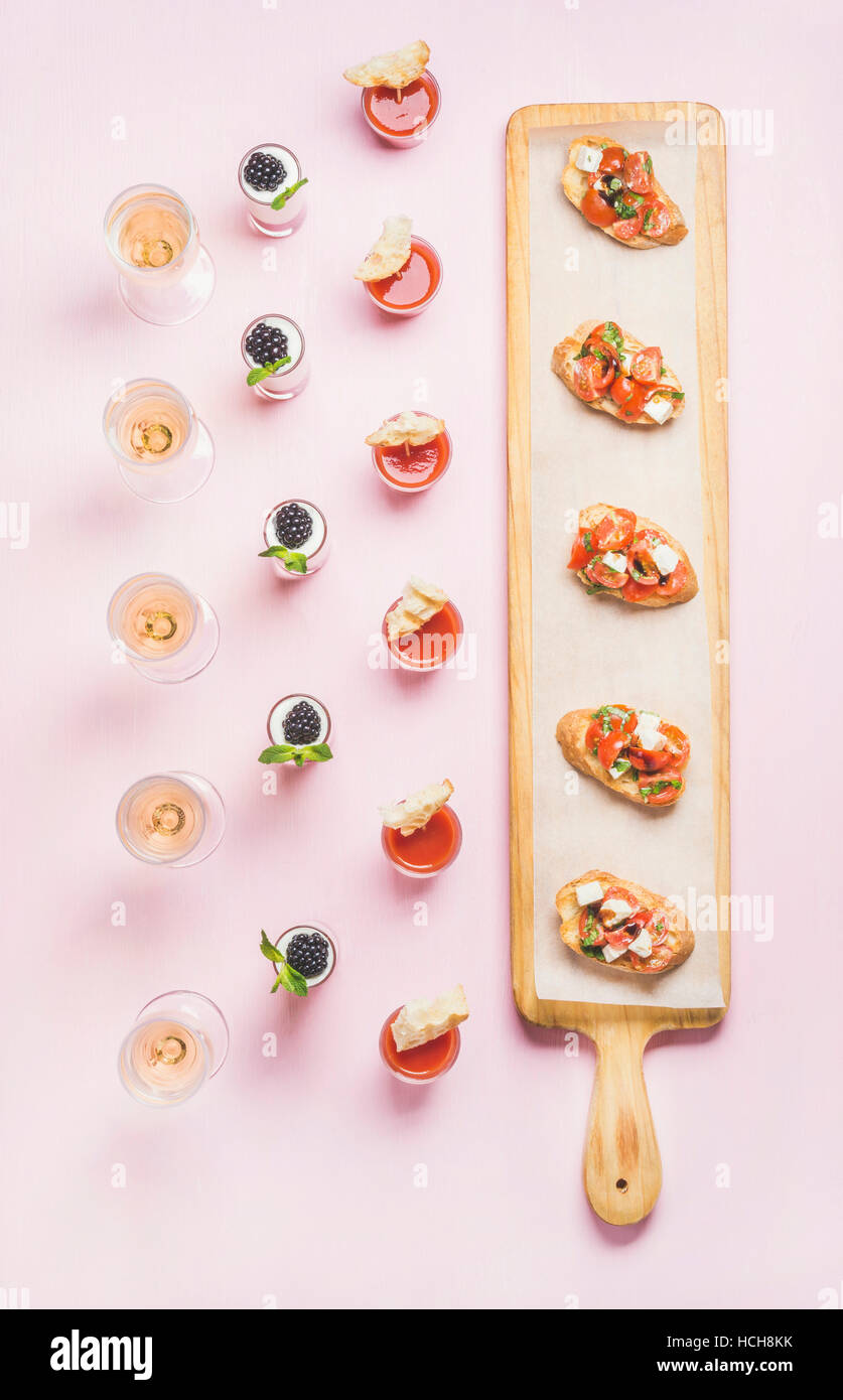 Catering, banquet food concept. Various snacks, brushetta sandwiches, gazpacho shots, desserts with berries on corporate - Stock Image