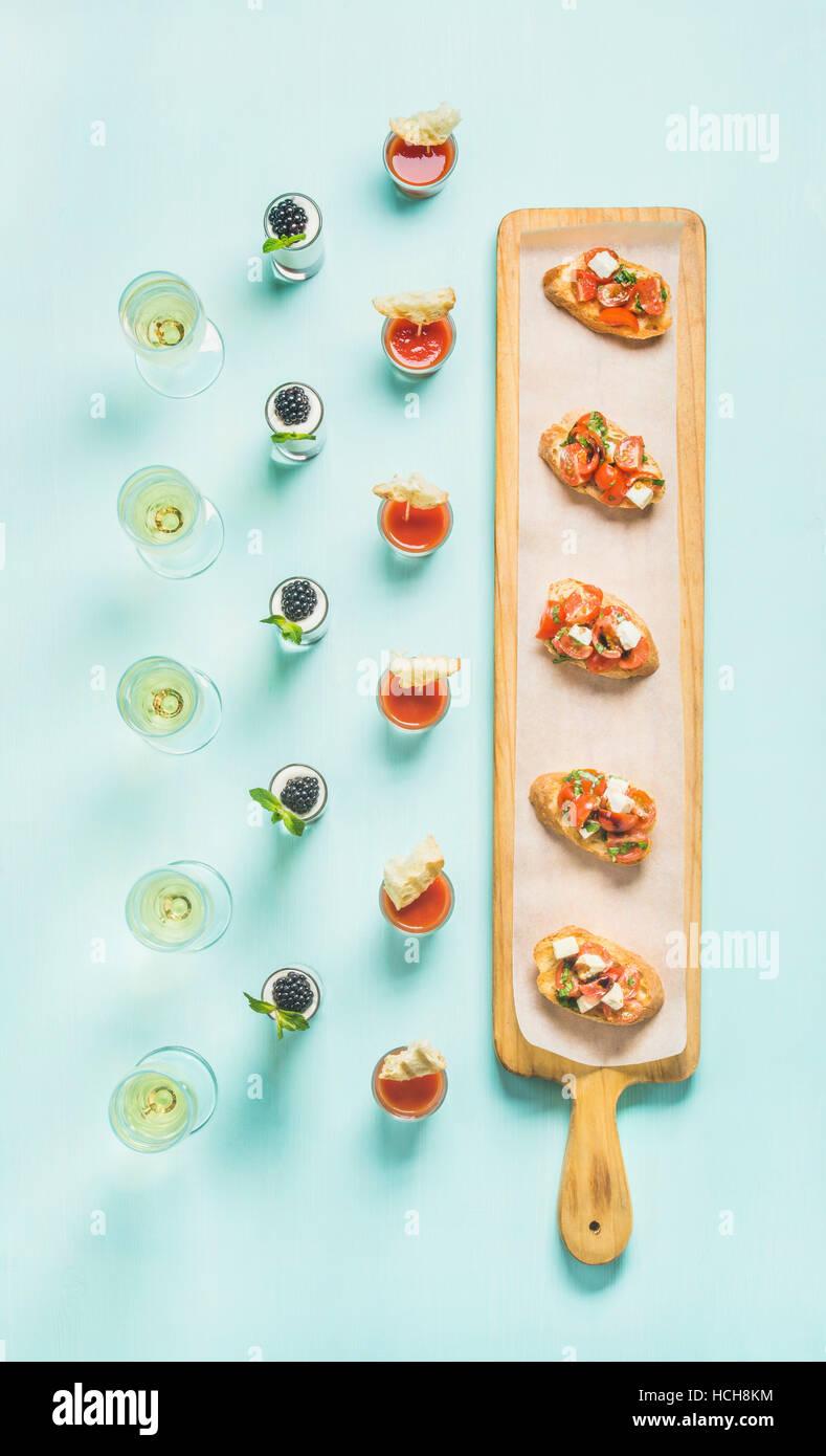 Various snacks, brushettas, gazpacho shots, desserts with berries and champagne on corporate event, christmas, birthday, - Stock Image