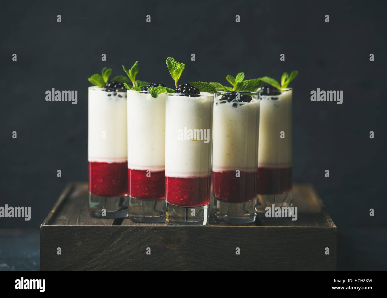 Catering, banquet or party food concept. Dessert in glass with blackberries and mint leaves over dark background - Stock Image