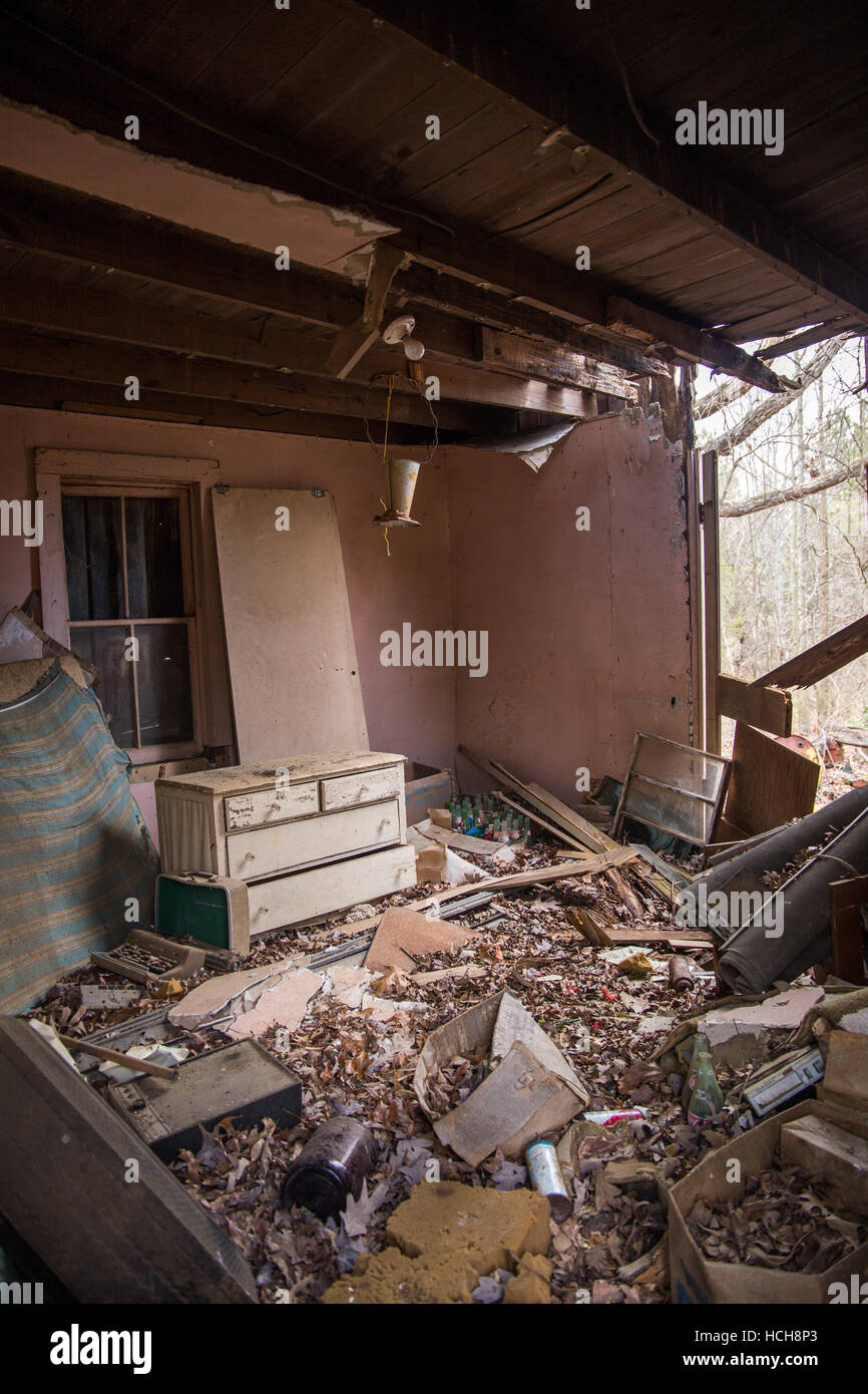 Wide angled view of empty room of an abandoned house with exposed ceiling and a dresser with floor full of junk - Stock Image