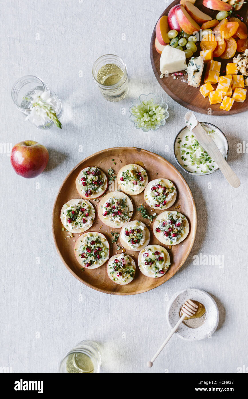 Sliced apples used as crackers and topped off with cheese, celery, pomegranate seeds, and walnuts. Photographed - Stock Image