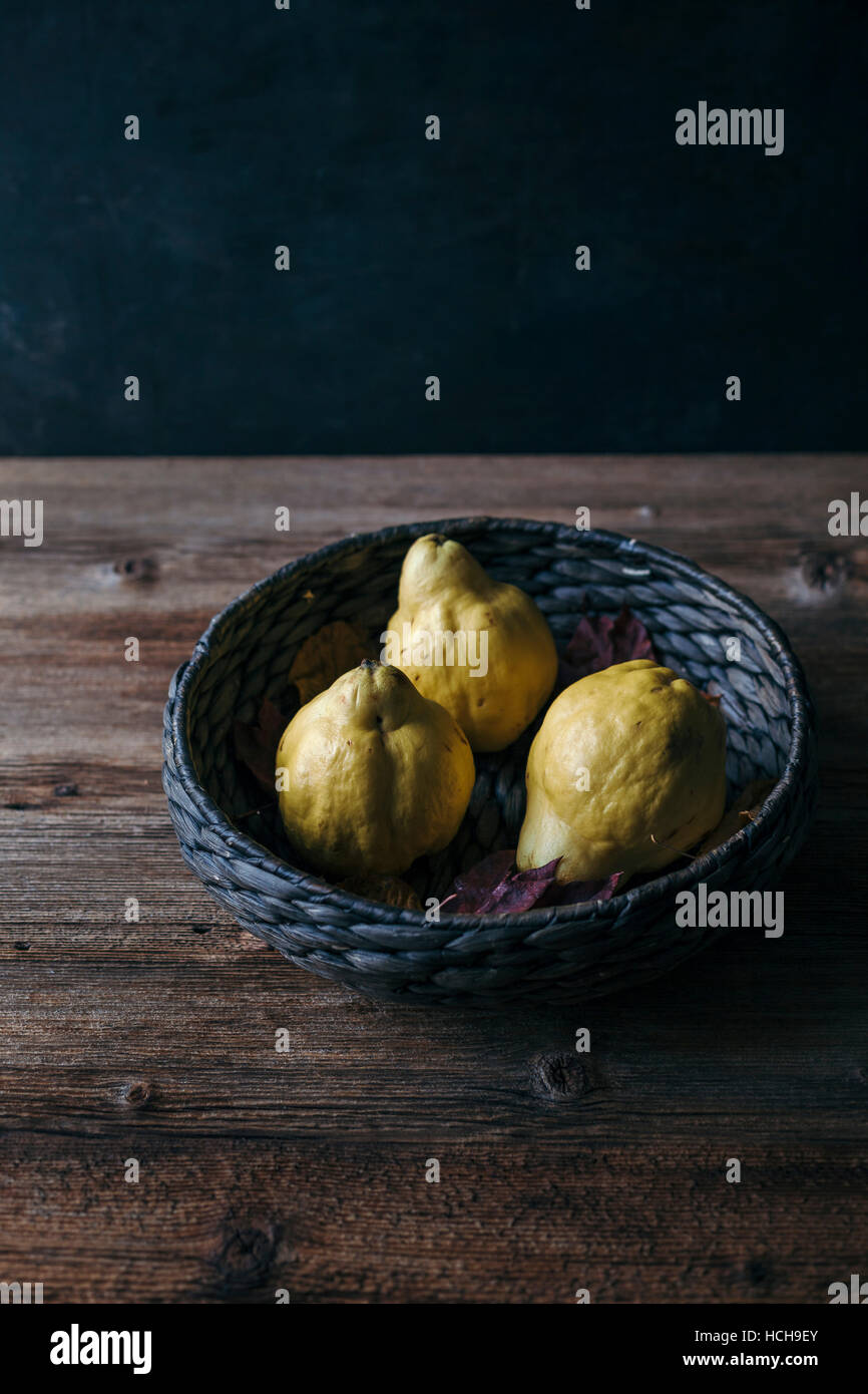 Quince in basket on rustic wooden table Stock Photo