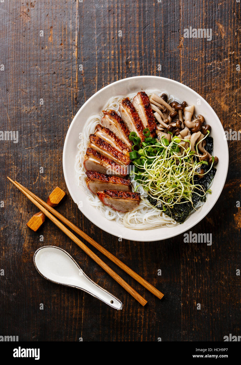 Rice noodles bowl with Peking Duck and mushrooms on wooden background Stock Photo