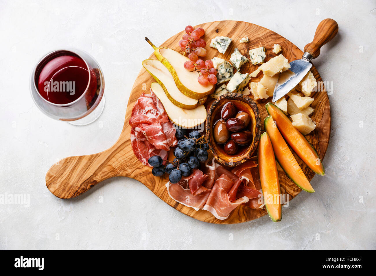 Meat and cheese plate antipasti snack with Prosciutto ham Parmesan Blue cheese Cantaloupe melon and Olives on olive wood serving board on concrete : cheese dessert plate - pezcame.com