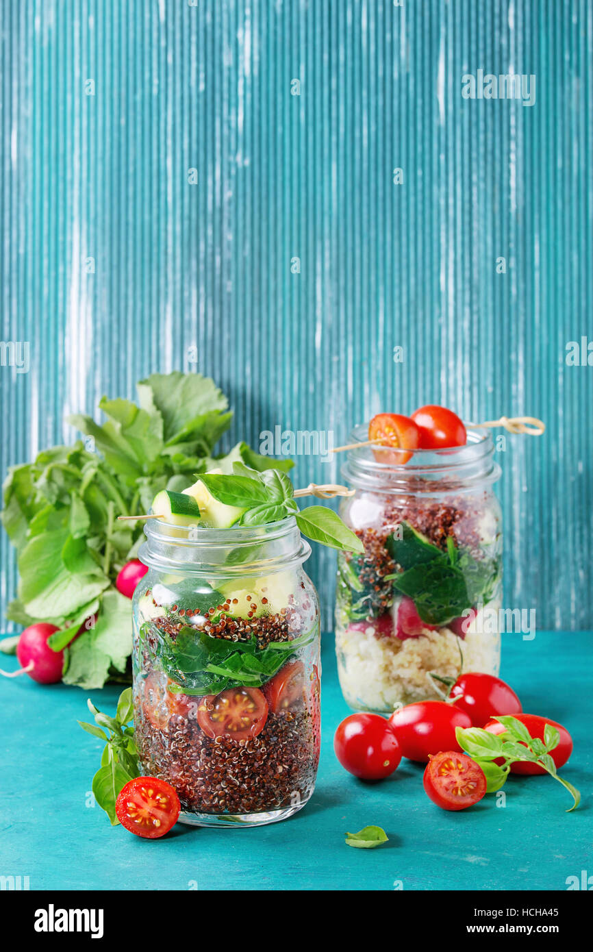 Salads with quinoa, couscous, spinach, radish, tomatoes and zucchini in glass mason jars, standing with fresh vegetables - Stock Image