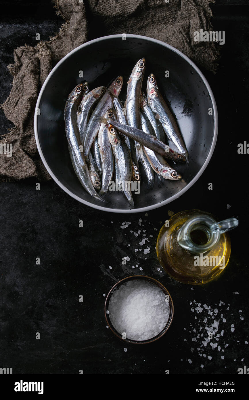 Lot of raw fresh anchovies fishes in black ceramic bowl with sea salt and bottle of olive oil for marinade over - Stock Image
