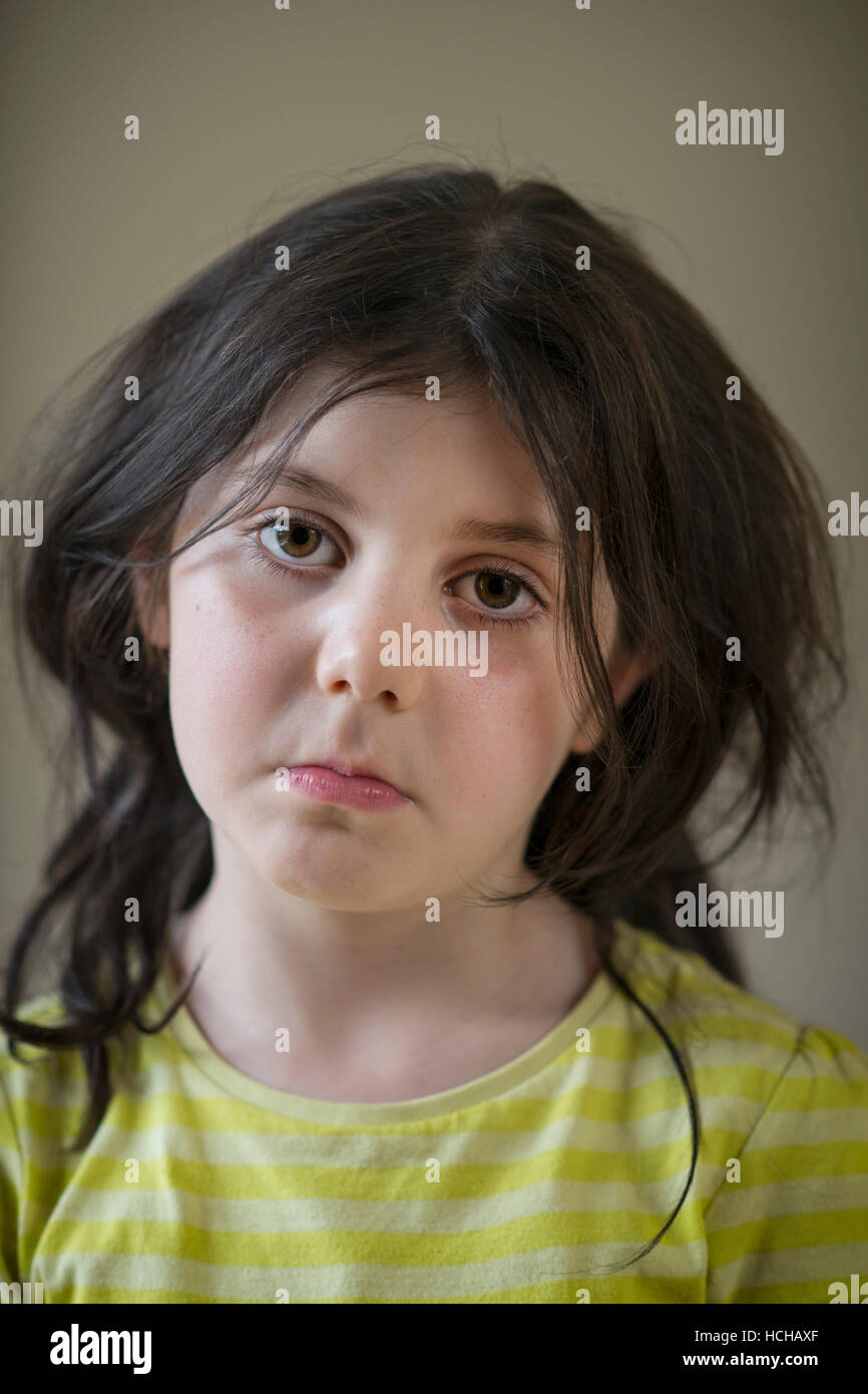 reflective sad looking young girl staring into the distance - Stock Image
